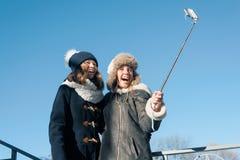 Zwei junge Jugendlichen, die Spaßfreien haben, glückliche lächelnde Freundinnen in der Winterkleidung, die selfie nimmt, positive lizenzfreie stockfotografie