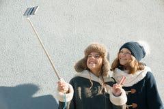 Zwei junge Jugendlichen, die Spaßfreien haben, glückliche lächelnde Freundinnen in der Winterkleidung, die selfie nimmt, positive stockfoto