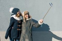 Zwei junge Jugendlichen, die Spaßfreien haben, glückliche lächelnde Freundinnen in der Winterkleidung, die selfie nimmt, positive stockbilder