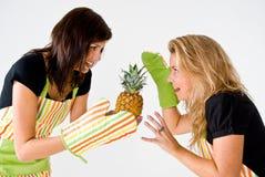 Zwei junge Köche mit Ananas lizenzfreie stockbilder