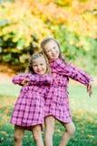 Zwei junge kaukasische Schwestern schlagen eine Haltung, wenn sie rosa Flanell-Kleider zusammenbringen lizenzfreie stockfotos