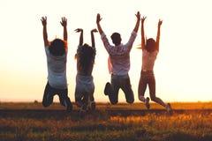 Zwei junge Kerle und zwei Mädchen halten ihre Hand und springen auf dem Gebiet an einem Sommertag Rückseitige Ansicht stockfotos