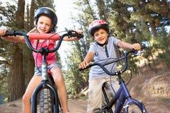 Zwei junge Kinder, die eine Fahrradfahrt genießen Stockbilder