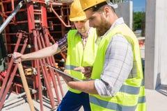 Zwei junge lächelnde Bauarbeiter bei der Anwendung eines Tablette duri Stockfotos