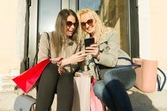Zwei junge lächelnde Frauen auf einer Stadtstraße mit Einkaufstaschen, sonniger Herbsttag, goldene Stunde stockfoto