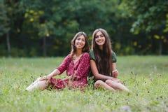 Zwei junge lächelnde Frauen, die auf Gras sitzen lizenzfreie stockbilder