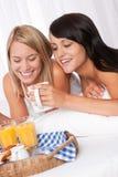 Zwei junge lächelnde Frauen, die frühstücken Lizenzfreies Stockfoto