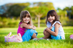 Zwei junge lächelnde Mädchen, die im Gras sitzen lizenzfreies stockbild