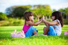 Zwei junge lächelnde Mädchen, die im Gras sitzen lizenzfreie stockfotos