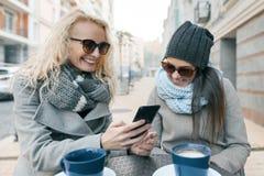 Zwei junge lächelnde moderne Frauen, die Spaß Café im im Freien haben Städtischer Hintergrund, Frauen, die Handy betrachtend lach stockfotos