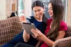 Zwei junge lachende Frauen bei der Anwendung einer Tablette Stockfotos
