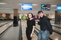Zwei junge Leute des Spaßes mit Bowlingkugeln in ihren Händen stehen auf dem Hintergrund der Bahn Stockbild