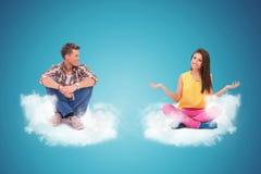 Zwei junge Leute, die auf dem Wolkenbegrüßen sitzen stockfoto