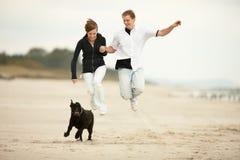 Zwei junge Leute, die auf den Strand und dem Anhalten springen Lizenzfreie Stockbilder