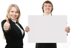 Zwei junge Leute, die ein weißes Zeichen anhalten Stockfotografie