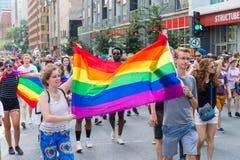 Zwei junge Leute, die eine große homosexuelle Regenbogenflagge halten stockbilder