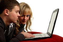 Zwei junge Leute, die an einer Laptop-Computer arbeiten Stockfotografie