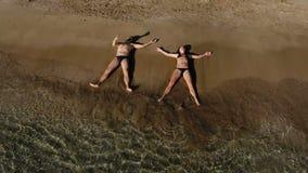 Zwei junge Leute entspannen sich auf dem Strand und den Wellen, die ihre Körper waschen stock video