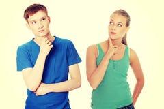 Zwei junge Leute mit dem Finger auf Kinn Lizenzfreie Stockbilder