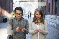 Zwei junge Leute mit intelligenten Telefonen Lizenzfreie Stockfotografie