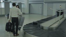 Zwei junge Leute warten ihr Gepäck nahe dem Gepäckausgabeschreibtisch im Flughafen stock video footage
