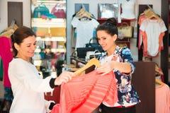 Zwei junge Mädchen in der Butike, die Kleid wählt Lizenzfreie Stockbilder