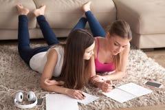 Zwei junge Mädchen, die auf dem Teppich, Kenntnisse in den Notizblöcken nehmend liegen Stockfotografie