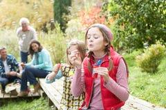 Zwei junge Mädchen, die draußen Luftblasen durchbrennen Stockfoto