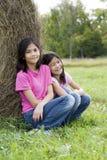 Zwei junge Mädchen, die durch haybale sitzen Lizenzfreie Stockbilder