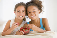Zwei junge Mädchen, die Erdbeeren essen Lizenzfreies Stockfoto