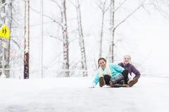 Zwei junge Mädchen, die hinunter Hügel im Eis und im Schnee rodeln Stockbild