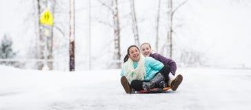 Zwei junge Mädchen, die hinunter Hügel im Eis und im Schnee rodeln Lizenzfreies Stockbild