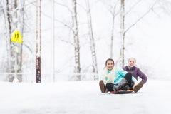 Zwei junge Mädchen, die hinunter Hügel im Eis und im Schnee rodeln Lizenzfreie Stockbilder