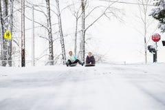 Zwei junge Mädchen, die hinunter Hügel im Eis und im Schnee rodeln Lizenzfreie Stockfotos