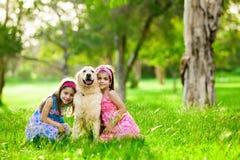 Zwei junge Mädchen, die Hund des goldenen Apportierhunds umarmen stockfotos