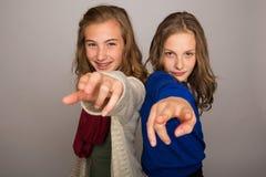 Zwei junge Mädchen, die ihre Finger auf Kamera zeigen Stockfoto