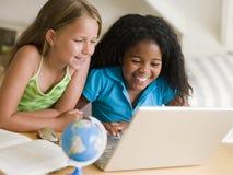 Zwei junge Mädchen, die ihre Heimarbeit auf einem Laptop tun Stockfotos