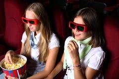 Zwei junge Mädchen, die im Kino überwachen stockfotografie