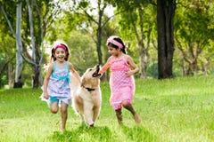 Zwei junge Mädchen, die mit goldenem Apportierhund laufen lizenzfreie stockbilder