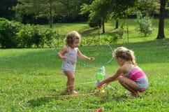 Zwei junge Mädchen, die mit Spielzeugberieselungsanlage spielen Stockbild