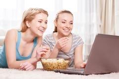 Zwei junge Mädchen, die Popcorn essen Stockbilder
