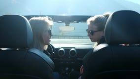 Zwei junge Mädchen in einem Cabriolet nahe dem Hochgebirge Gespräch hinter dem Rad Mädchen korrigiert Autorückspiegel stock video