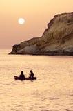 Zwei junge Mädchen entspannen sich auf ihrem aufblasbaren und genießen den Sonnenuntergang Stockbild