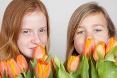 Zwei junge Mädchen halten rosafarbene orange Tulpen an Lizenzfreies Stockfoto