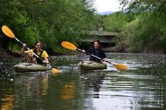 Zwei junge Mädchen und ein Kayak fahrender Hund stockfotos