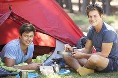 Zwei junge Männer, die auf kampierendem Ofen außerhalb des Zeltes kochen Lizenzfreies Stockfoto