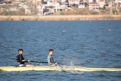 Zwei junge Männer, die das Kayak fahren in einem See üben lizenzfreies stockbild