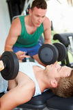 Zwei junge Männer, die in der Turnhalle mit Gewichten ausbilden Lizenzfreies Stockbild
