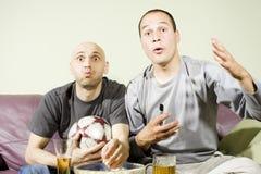 Zwei junge Männer, die eine Fußbalabgleichung auf Fernsehapparat überwachen Lizenzfreies Stockbild