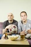 Zwei junge Männer, die eine Fußbalabgleichung auf Fernsehapparat überwachen Lizenzfreie Stockfotos